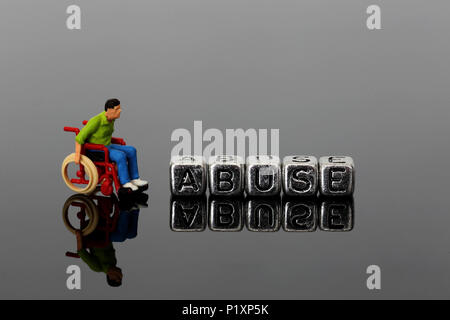 Miniature scale model man in a wheelchair with the word abuse on beads reflected on a dark background - Stock Photo