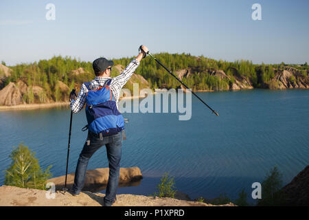 Image from back of young tourist with backpack with arms raised with walking sticks on background of mountain landscape - Stock Photo