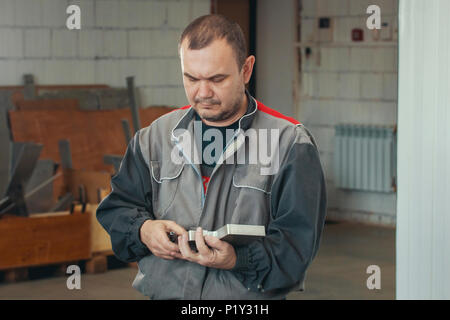 Adult man in uniform working with metal detail at CNC machine at factory with lathes - Stock Photo