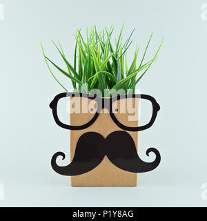 Cheerful funny face on paper bag with glasses and mustache, and hair from the grass. Back to School concept, square format - Stock Photo