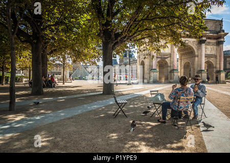 French couple enjoying a snack in a park near the Louvre, framed by trees. - Stock Photo