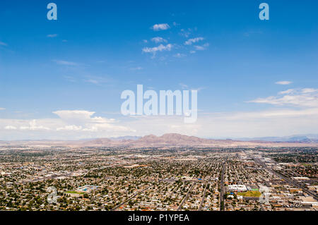 Landscape view of the residential area of Las Vegas, photographed from the top of the Stratosphere Hotel.  Set against a blue sky, with some white cloud, and mountains on the horizon.  Copy space. - Stock Photo