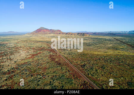 Aerial view of great northern highway and Mount Bruce in outback landscape, Pilbara, Northwest Australia - Stock Photo