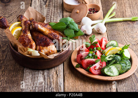 Roasted chicken drumsticks in ceramic bowl and fresh vegetables on rustic wooden table, favorite meal - Stock Photo