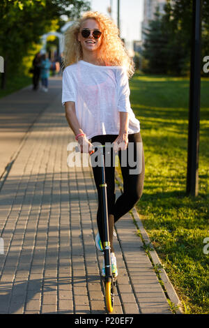 Photo of curly-haired athletic woman riding scooter in park - Stock Photo