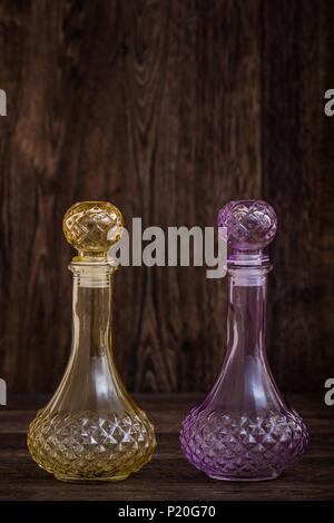 Decorative colorful olive oil and vinegar bottles on brown background - Stock Photo
