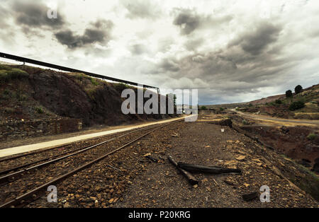 Old railroad track in the mines, with pebbles and burned woods on the sides at the Zaranda train station, Spain - Stock Photo