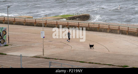 Brighton UK 14th June 2018 - A runner out on Brighton seafront on a windy morning by the Marina as Storm Hector sweeps across Britain with high winds and rain causing travel problems and damage in some parts of the country Credit: Simon Dack/Alamy Live News - Stock Photo
