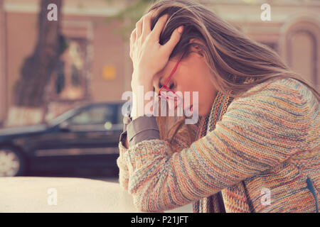 Side profile stressed sad young woman sitting outdoors with broken down car on background. City urban life style stress - Stock Photo