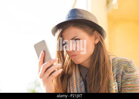 Young woman in hat watching smartphone and looking angry having bad message on urban background. - Stock Photo