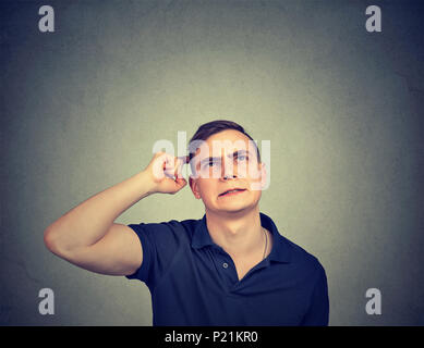 Closeup portrait man scratching head, thinking about something, looking up, isolated on gray wall background. - Stock Photo