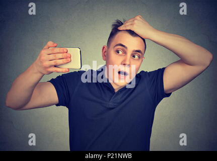 Portrait shocked man feeling head, surprised he is losing hair isolated on gray background. Negative facial expressions, emotion - Stock Photo