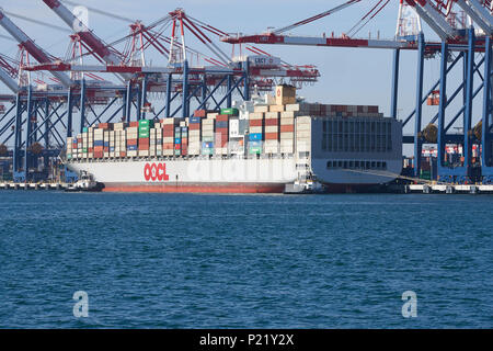 Container Ship, OOCL LONDON, About To Depart The Long Beach Container Terminal. Tugs Waiting Fore And Aft. Port Of Long Beach, California, USA. - Stock Photo