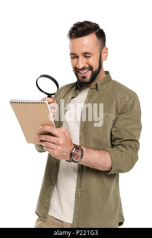portrait of smiling man looking at notebook through magnifying glass isolated on white - Stock Photo
