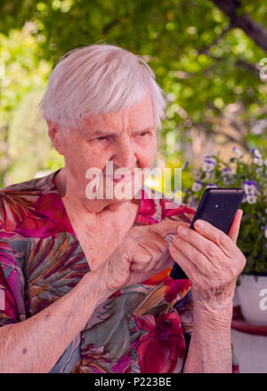 Smiling elderly woman dialing phone number one of her relative. - Stock Photo