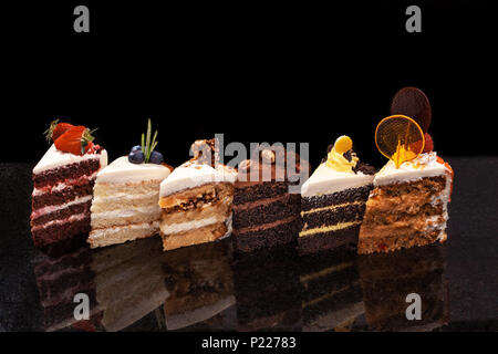 Assorted large pieces of different cakes: chocolate, raspberries, strawberries, nuts, blueberries. Pieces of cakes on a black table. - Stock Photo