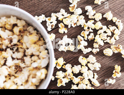 directly above close-up of bowl filled with popcorn on rustic wooden table - Stock Photo