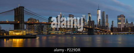 Panoramic long exposure of the Brooklyn Bridge and Manhattan skyline at dawn from across the East River in Brooklyn, New York, USA - Stock Photo