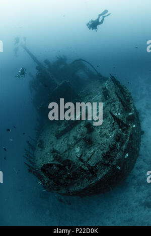 underwater ship wreck with scuba divers - Stock Photo
