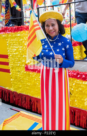 An immigrant wearing a stars and stripes dress and waving a South Vietnamese flag at the Vietnamese American Cultural Parade. - Stock Photo