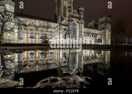 Durham Cathedral exterior is lit up at night, and is reflected in a puddle on the ground outside - Stock Photo