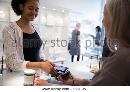 Young woman with smart phone paying with contactless payment in boutique - Stock Photo