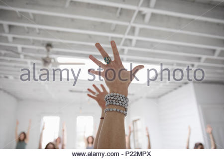Woman with arms raised wearing mala beads in yoga class - Stock Photo
