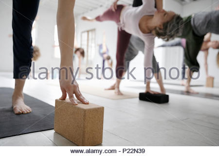 Women practicing half moon pose with blocks in yoga class - Stock Photo