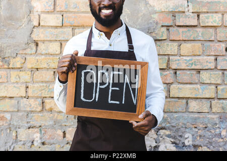 cropped shot of smiling young african american barista holding sign open while standing near brick wall - Stock Photo