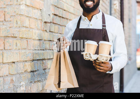 cropped shot of smiling young african american barista holding paper bags and disposable coffee cups - Stock Photo
