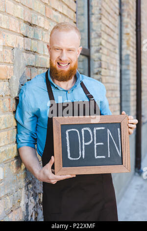 handsome bearded young barista holding sign open and smiling at camera - Stock Photo
