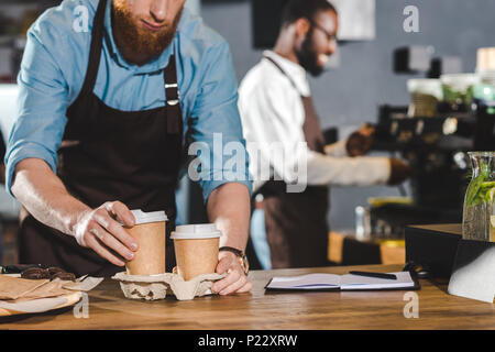 cropped shot of male barista in apron putting paper cups of coffee in cardboard and smiling colleague using coffee machine behind - Stock Photo