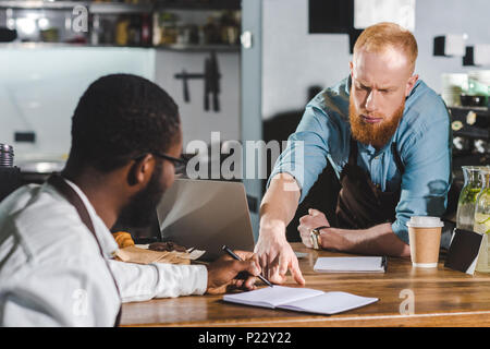 young serious male barista pointing by finger on textbook to colleague - Stock Photo