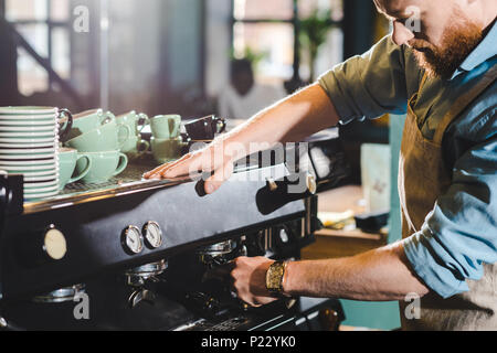 cropped image of young male barista in apron using coffee machine - Stock Photo