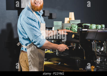 cropped image of male barista in apron using coffee machine - Stock Photo