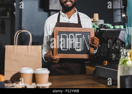 cropped shot of smiling african american barista holding sign open in coffee shop - Stock Photo