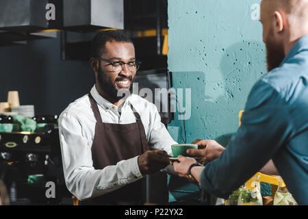 cropped shot of smiling african american barista giving cup of coffee to bearded client in coffee shop - Stock Photo