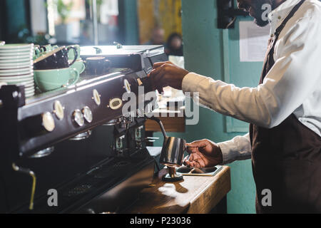 cropped shot of smiling african american barista making cappuccino at coffee machine - Stock Photo