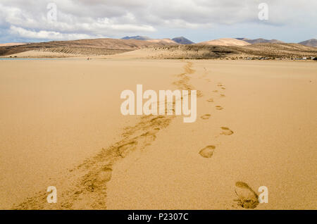 Footprints on the sandy beach of Sotavento, Fuerteventura, Canary Islands with a mountain range and stormy sky - Stock Photo