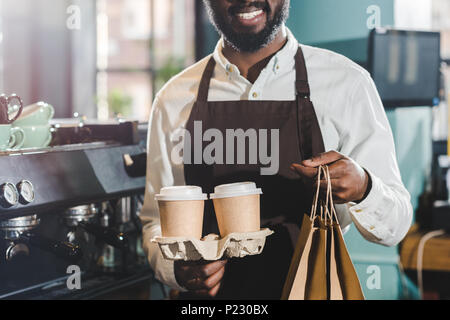 cropped shot of smiling african american barista holding paper bags and disposable coffee cups in cafe - Stock Photo
