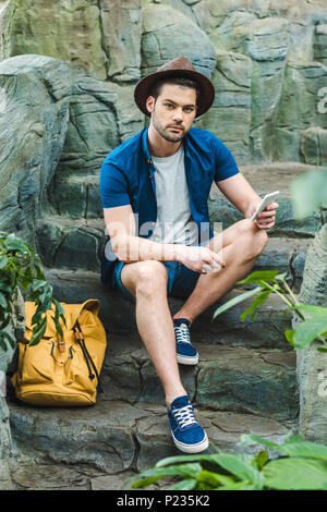 attractive young man using smartphone while sitting on stone staircase - Stock Photo