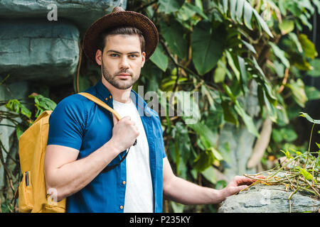 handsome young man in stylish clothes in rainforest - Stock Photo