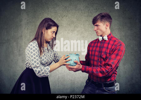 Finances in divorce concept. Angry wife and husband can not make settlement holding piggy bank looking at each other with hatred - Stock Photo