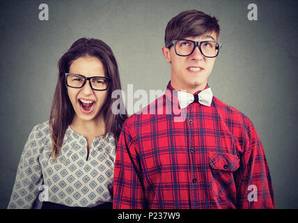 Angry mad woman screaming and fearful annoyed stressed man - Stock Photo