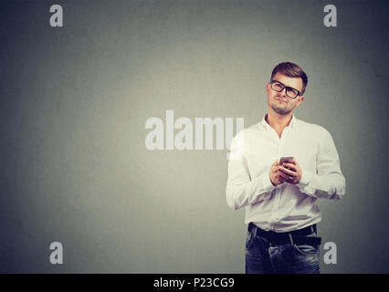 Handsome man in glasses holding phone in hands and looking up in contemplation on gray backdrop. - Stock Photo