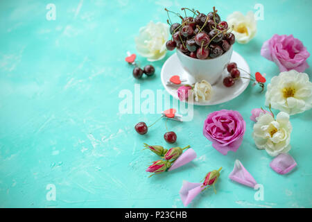 White cup of sweet cherry berries with roses and flowers on a green emerald background.ripe cherries and wild roses. Flat lay, top view sweet food floral background. Copy space