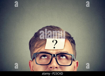 Young man wearing black glasses with question mark on forehead looking up. - Stock Photo