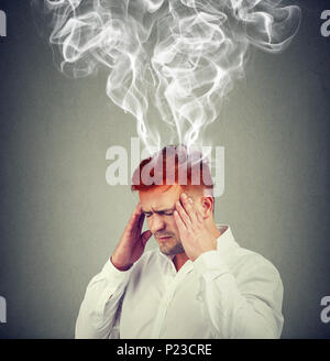 Conceptual shot of man holding hands on temples and looking frustrated with smoke coming out of head. - Stock Photo