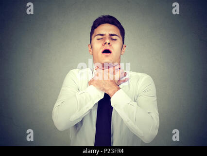 Young man having asthma attack or choking can't breath suffering from respiration problems isolated on gray background - Stock Photo