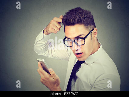 Shocked man feeling head, surprised he is losing hair, receding hairline isolated on gray background. - Stock Photo